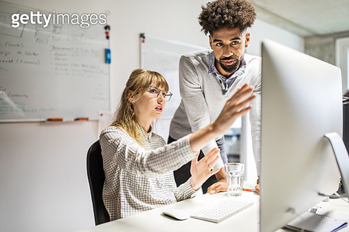 Businesswoman and businessman discussing over computer in office - gettyimageskorea
