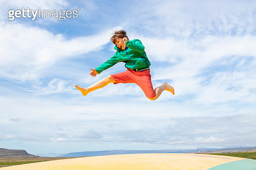 cute and young boy is bouncing off an air trampoline - gettyimageskorea