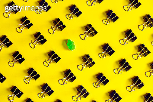 Binder clips and green jelly bean frog on yellow background - gettyimageskorea