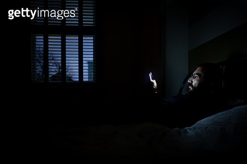 A man lying on bed and reading a book from electronic book reader - gettyimageskorea