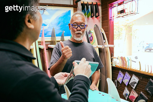 Shopkeeper who presents the amount of surfboards to customers in shop - gettyimageskorea