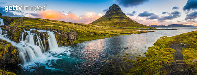 The clear blue waters of Kirkjufellfoss waterfall tumbling down the mountainside to the ocean fjord beside Grundarfjordur beneath the iconic peak of Kirkjufell framed by the warm glow of sunrise over the Snaefellsnes peninsula in the far east of Iceland.  - gettyimageskorea