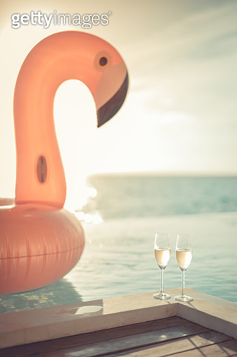 Luxury infinity swimming pool. Sunset holiday travel vacation background with funny flamingo toy float header an champagne glasses as romantic couple background, exotic love romance destination. - gettyimageskorea