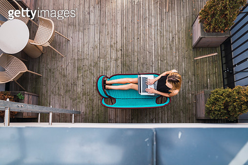 Young woman sitting on turquoise couch on terrace using laptop, top view - gettyimageskorea