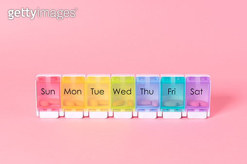 Multi Colored Weekly Pill Organizer on Pink Colored Background. - gettyimageskorea