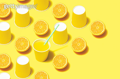 Disposable paper cups on color background. Yellow paper cups  and orange juice on yellow background. - gettyimageskorea