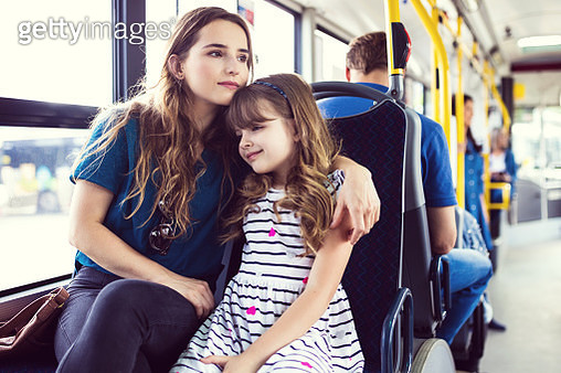 Mid adult woman traveling with daughter in bus. Girl is commuting with mother in public transport. They are sitting on seat together. - gettyimageskorea