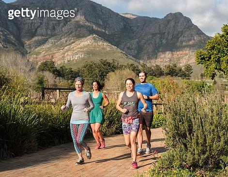 Full length shot of a runner group jogging together in a park - gettyimageskorea