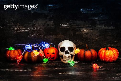 Jack O Lantern With Human Skull And Illuminated Lighting Equipment On Table - gettyimageskorea