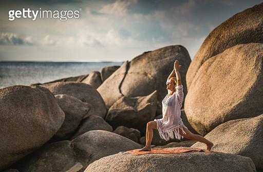 Relaxed woman doing Yoga meditation exercises during summer day on a beach rock. - gettyimageskorea
