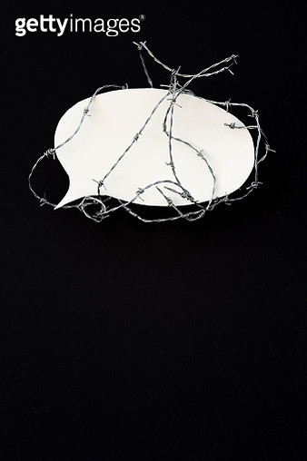 Barbed wire around a speech bubble made of paper. Black background. - gettyimageskorea
