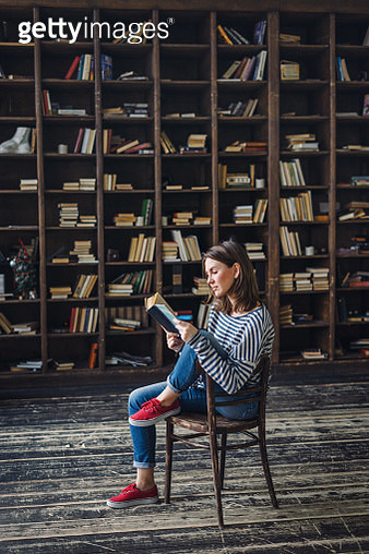 Young woman reading in the library - gettyimageskorea