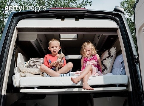 brother and sister sat on a bed in a camper van on vacation in summer - gettyimageskorea