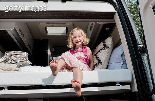 portrait of a young girl sat in bed in a camper van on vacation - gettyimageskorea