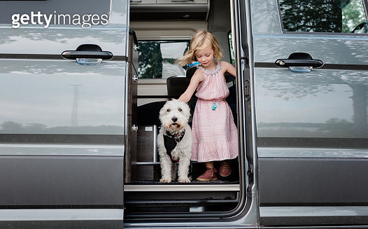 portrait of a young girl camping in a camper van with her dog - gettyimageskorea