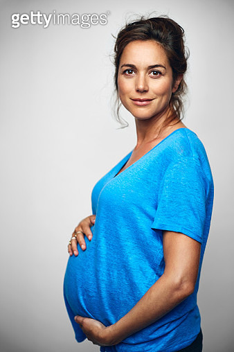 Side view of pregnant businesswoman with hands on stomach. Portrait of female professional is wearing casuals. Executive is standing over white background. - gettyimageskorea