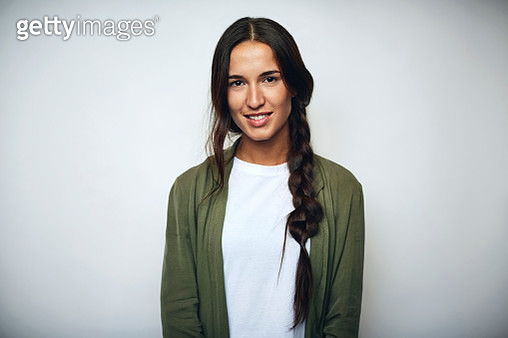 Portrait of businesswoman with braided hair. Confident female professional is wearing jacket. She is smiling over white background. - gettyimageskorea