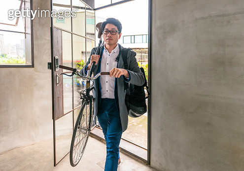 Young businessman arriving at work with his bike - gettyimageskorea