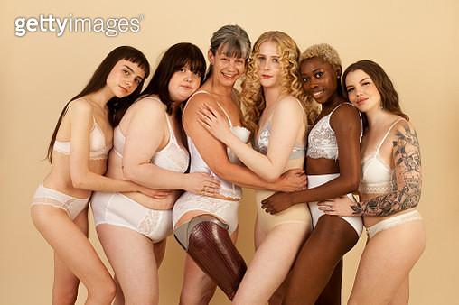 Five diverse and confident women hug in the studio - gettyimageskorea