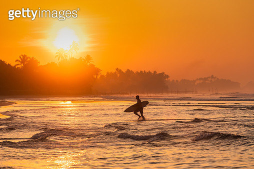 Surfer at sunrise on the shores of the Indian Ocean - gettyimageskorea