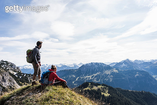 Austria, Tyrol, young couple in mountainscape looking at view - gettyimageskorea