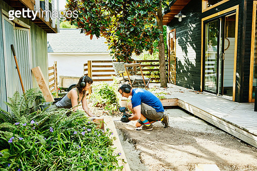 Couple building raised garden beds in backyard on summer afternoon - gettyimageskorea