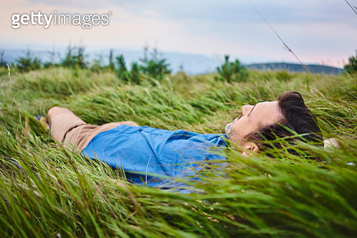 Relaxed man lying in grass - gettyimageskorea