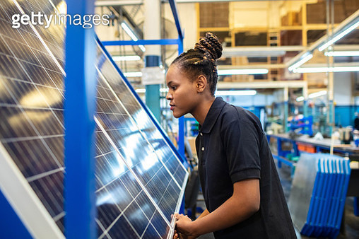 Quality engineer examining solar panels in factory - gettyimageskorea
