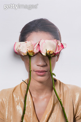 Young woman's eyes covered by roses - gettyimageskorea