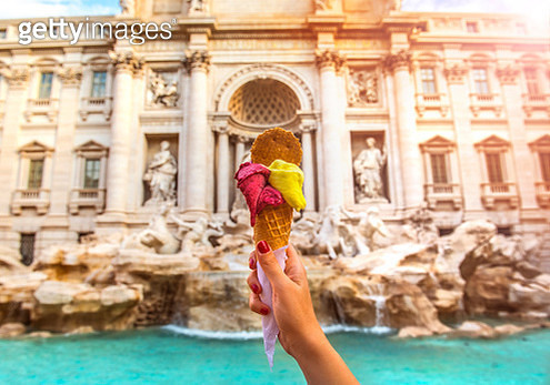 Hand holding colorful gelato in front of famous iconic Trevi Fountain at Rome, Italy. - gettyimageskorea