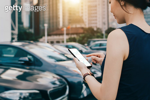 Woman looking into financial trading data on smartphone while walking to her car in outdoor car park - gettyimageskorea