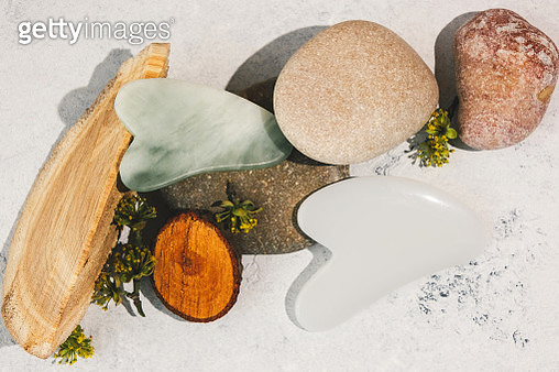 A variety of gua sha scrapers lie on stones and wood cuts - gettyimageskorea