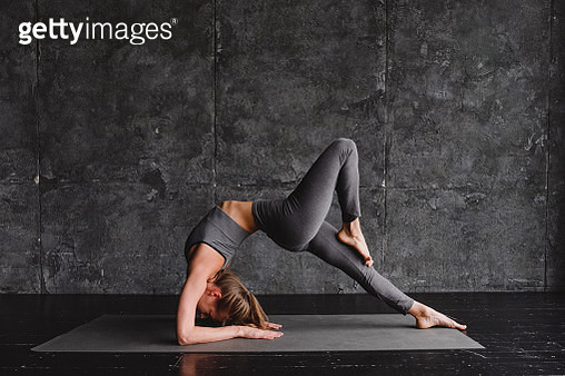 Young woman doing yoga on a gray background - gettyimageskorea
