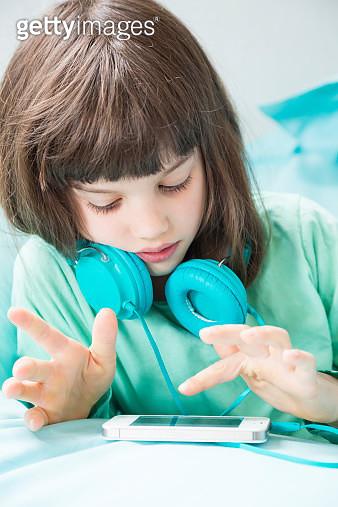 Portrait of little girl with headphones using smartphone - gettyimageskorea