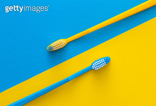 Toothbrushes on yellow and blue background. Health care concept. - gettyimageskorea