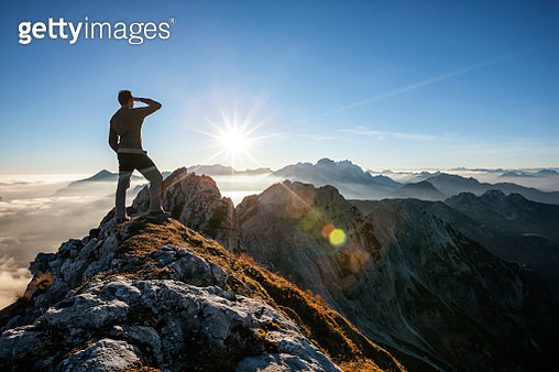 Climber standing on the mountain peak and watching the sun - gettyimageskorea