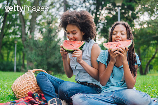 Happy girls eating watermelon on a picnic - gettyimageskorea