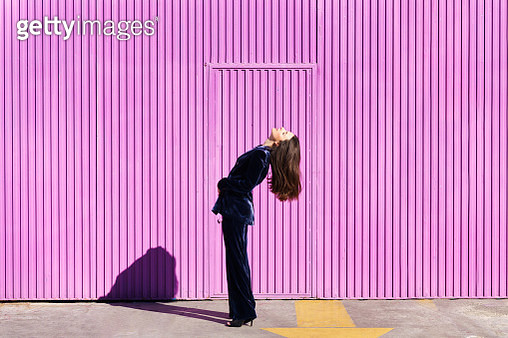 Side View Of Woman Standing Against Pink Wall - gettyimageskorea