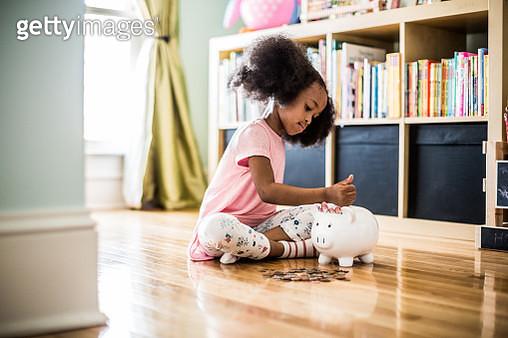 girl putting money in piggybank - gettyimageskorea