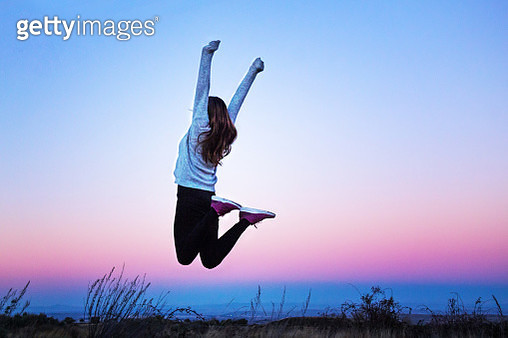 Young woman jumping raising her arms at a colorful sunset - Aragon, Spain - gettyimageskorea