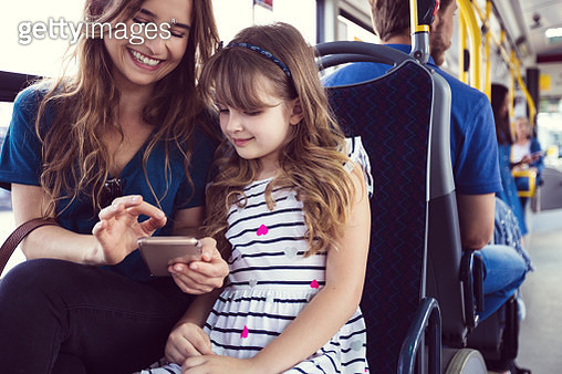 Mid adult woman showing mobile phone to daughter in bus. Girl is traveling with mother in public transport. They are sitting on seat. - gettyimageskorea
