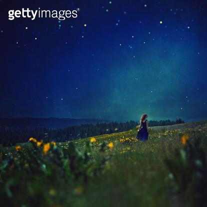 Woman in dress in meadow under stars, Oregon - gettyimageskorea