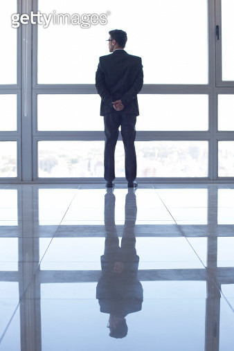 Man standing in front of window, looking at view - gettyimageskorea