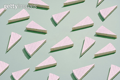 a large group of brie cheese pieces placed in a repetative pattern on a colored background - gettyimageskorea