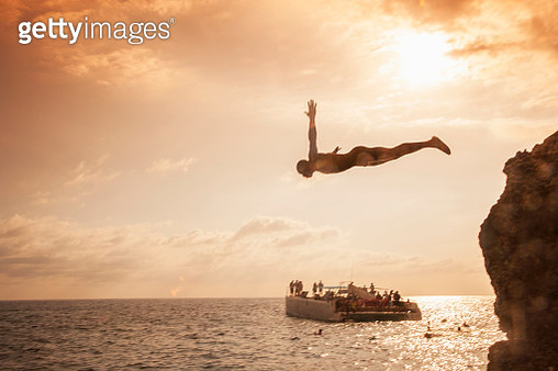 Jamaican man diving fro a rocky cliff at sunset while tourists on a catamaran are watching him - gettyimageskorea