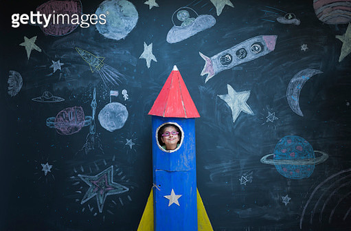Portrait of girl in handmade space rocket in front of space themed chalk drawings - gettyimageskorea