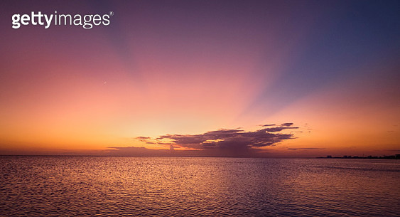 Beautiful sunrays in pink and blue against orange colors at sunset at Fort Myers Beach, Florida in October. - gettyimageskorea