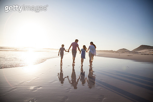 Family walking together on a beach at sunset - gettyimageskorea