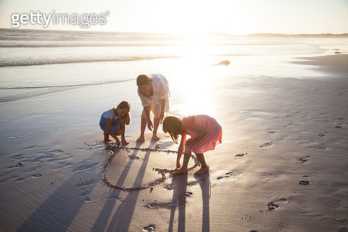 Mother and daughters playing together making heart shapes on a beach at sunset - gettyimageskorea