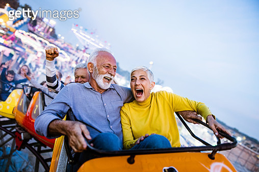 Cheerful senior couple having fun while riding on rollercoaster at amusement park. Copy space. - gettyimageskorea